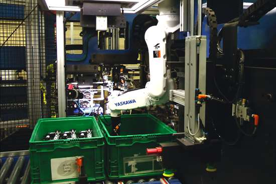 A vision-guided Yaskawa robot picks an actuator assembly from a bin.