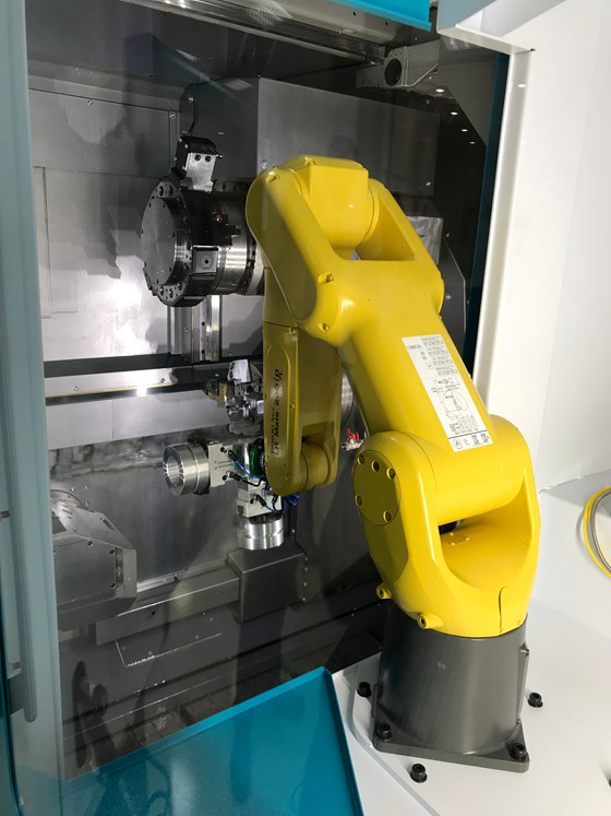 As seen through the window of an iXcenter cell, a Fanuc LR Mate 200 iD 7L robot loads a blank into the C200 turning center.