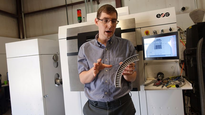 Jacob Nuechterlein with EOS machine and metal matrix composite part