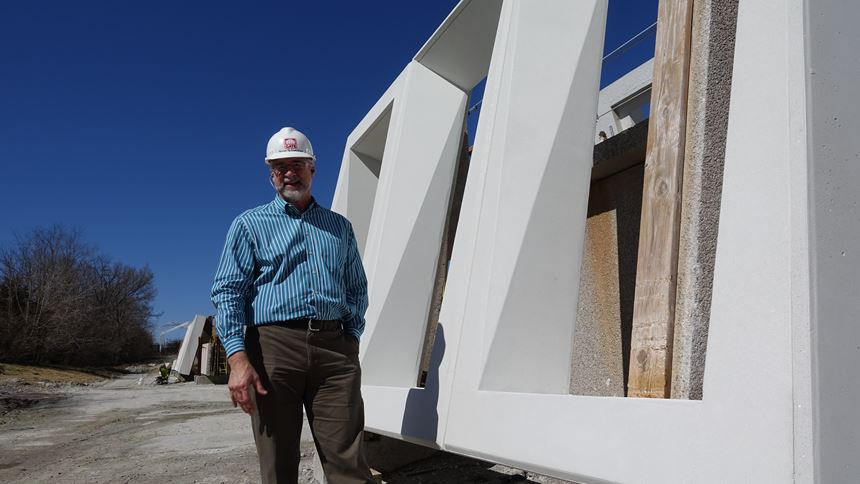 Steve Schweitzer in front of precast concrete punched windows
