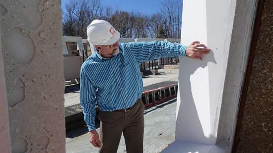 Steve Schweitzer pointing to precast concrete punched window