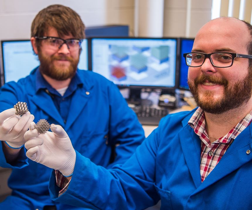 Carpenter Technology engineers holding 3D-printed parts at the AM lab