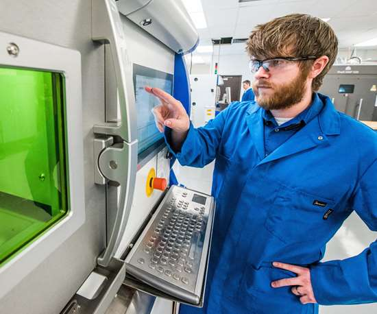 Carpenter Technology engineer running a metal 3D printing system