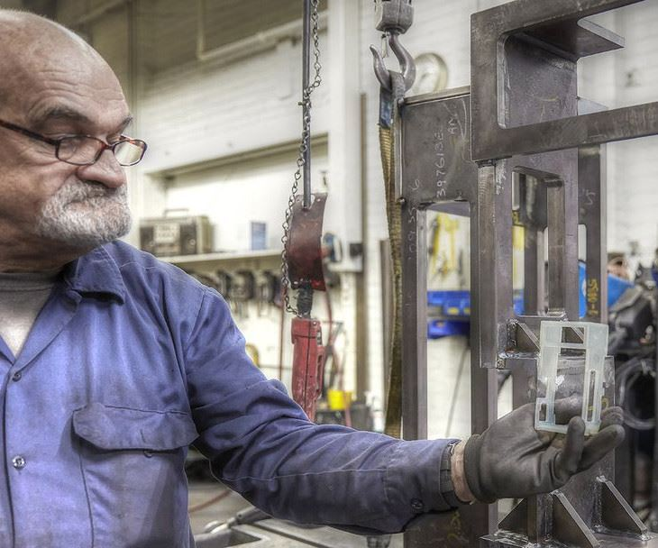 A&M Tool and Design employee holding a 3D-printed object