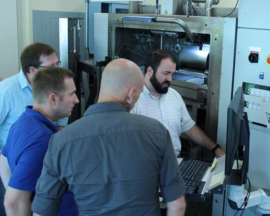 Students receiving instruction in setting up a metal AM machine from 3D Systems
