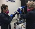 wearing respirator while loading metal powder into okuma hybrid additive manufacturing machine