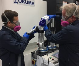 wearing respirator while loading metal powder into okuma hybrid additive manufacturing machine