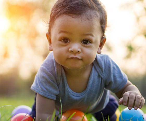 Crawling baby among balls