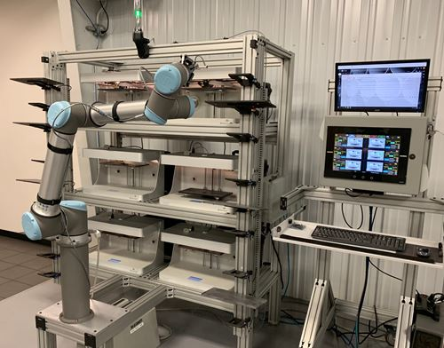 Cobot in front of cell with computers visible