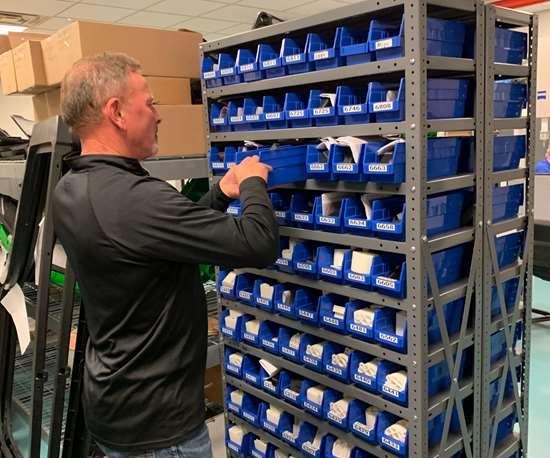employee retrieving fixtures from bin