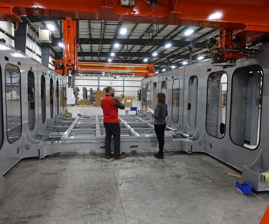 Jason Susnjara and Stephanie Hendrixson standing inside an unfinished LSAM machine