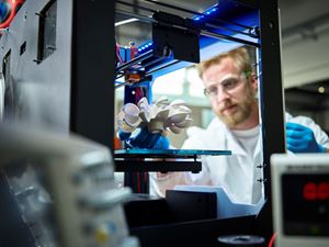 Person viewing 3D printing of a part