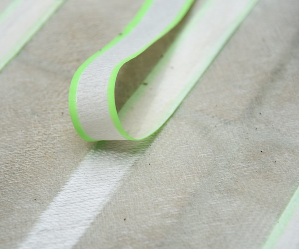 Masked fabric to create seams for foldable composite.