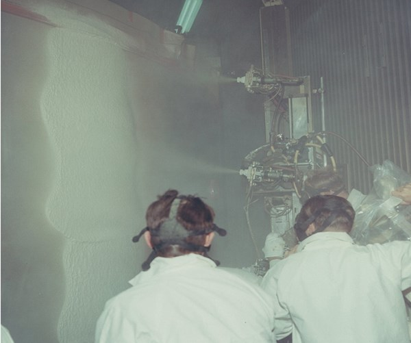 Workers spray polyurethane foam onto the Saturn V S-2 section.