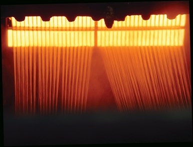 molten glass extruded through heated bushing plates