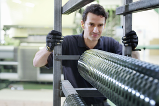 worker moving a roll of composite material