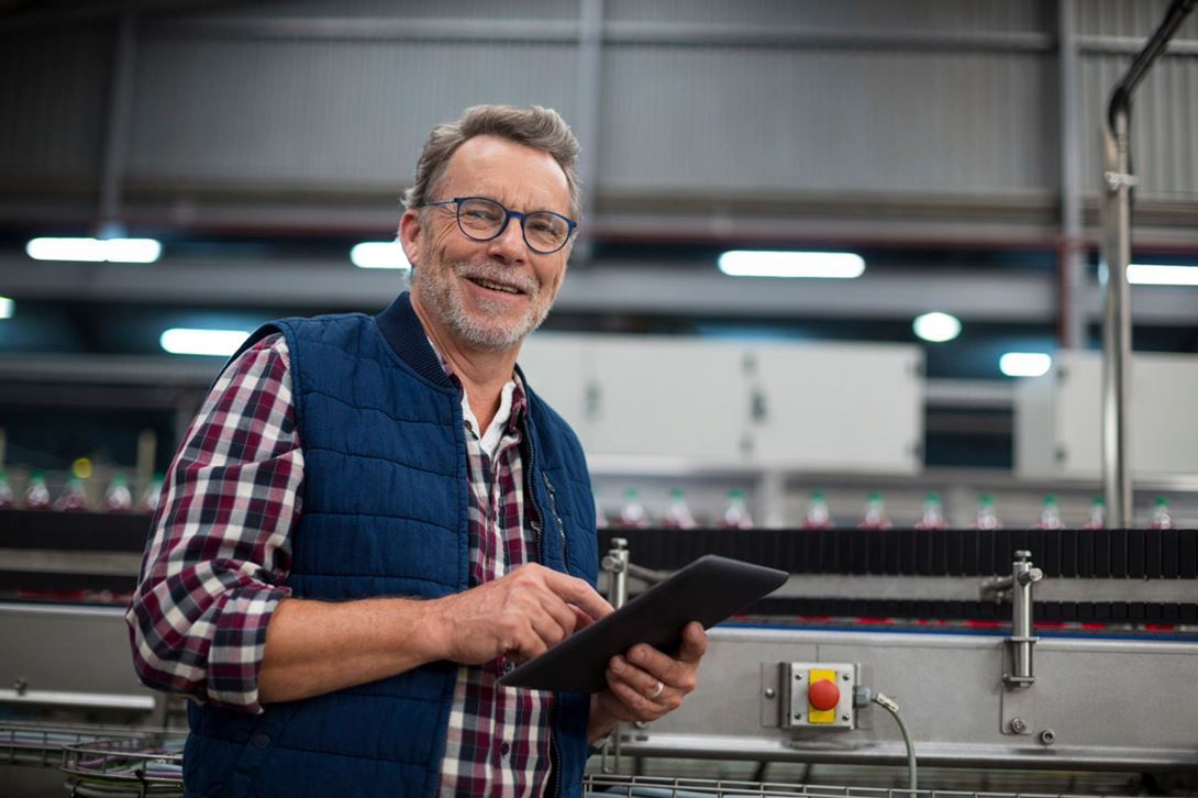 Man in a job shop holding a tablet