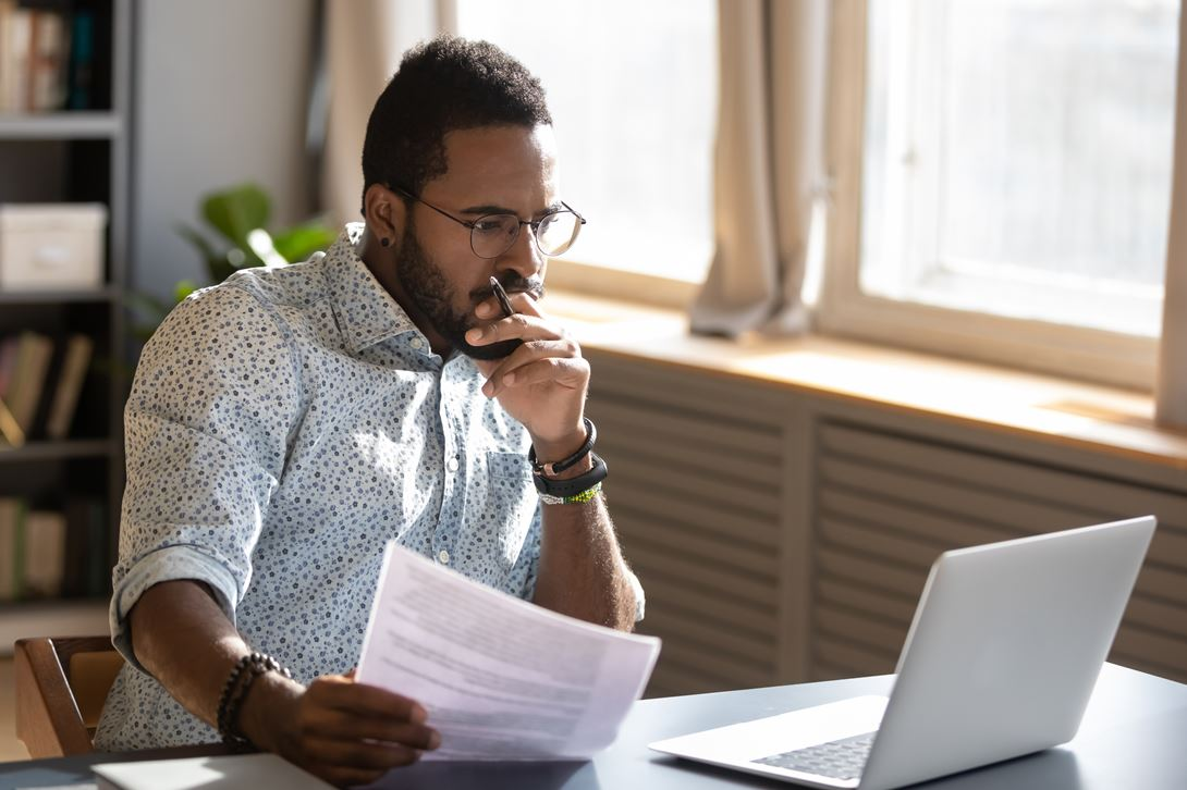 Man with Sleeves rolled up looking at laptop