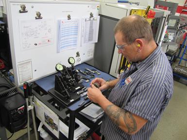 Bob Zimmer comprueba una parte en la estación de medición en su máquina.
