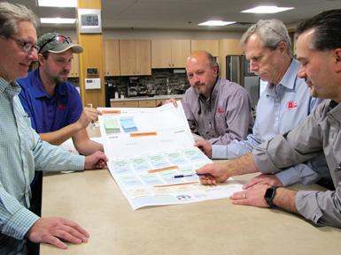 Mike Preston (al fondo a la izquierda) y Dan Vermeesch (al fondo a la derecha) revisan una plantilla Kata, que analiza procedimientos de rutina como el setup de la máquina
