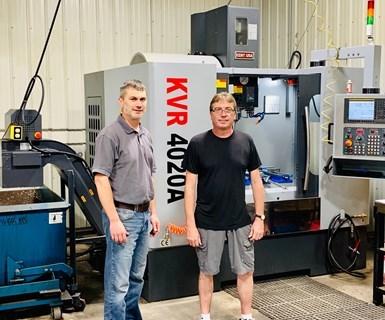 El líder de taller, Andy Hass (a la izquierda), junto a Jason Davies, presidente de Journeyman Machine and Supply Co. Detrás de ellos hay un nuevo centro de mecanizado vertical Kent KVR 4020A.