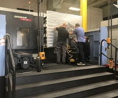 De izquierda a derecha, el gerente general, Greg Carroll, el presidente y CEO, Daniel Marton, y el operario de máquinas de cinco ejes, Miguel Chávez, inspeccionan un gran componente estructural aeroespacial de aluminio fuera de un centro de mecanizado horizontal Doosan HM1250 de cuatro ejes.
