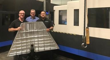 Greg Carroll, Daniel Marton y Miguel Chávez muestran un gran componente estructural aeroespacial de aluminio.