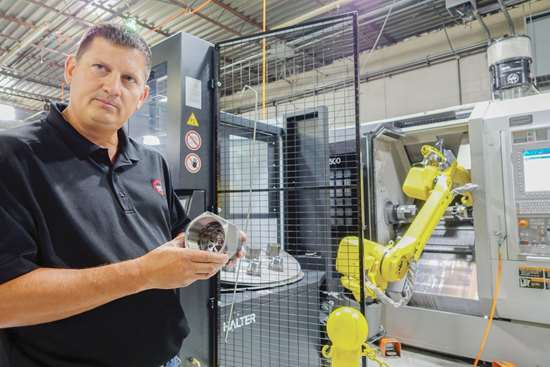 John Hicks holds a part in front of a robot cell