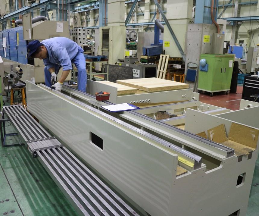 Technician hand scraping the ways on a Mitsui Seiki machine tool base