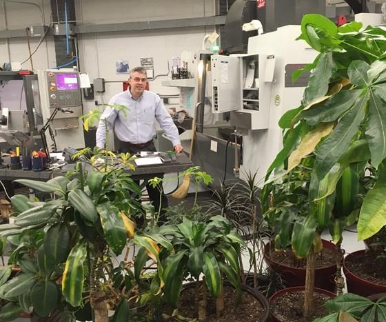 Zelinski stands among plants on shop floor at L&S Machine
