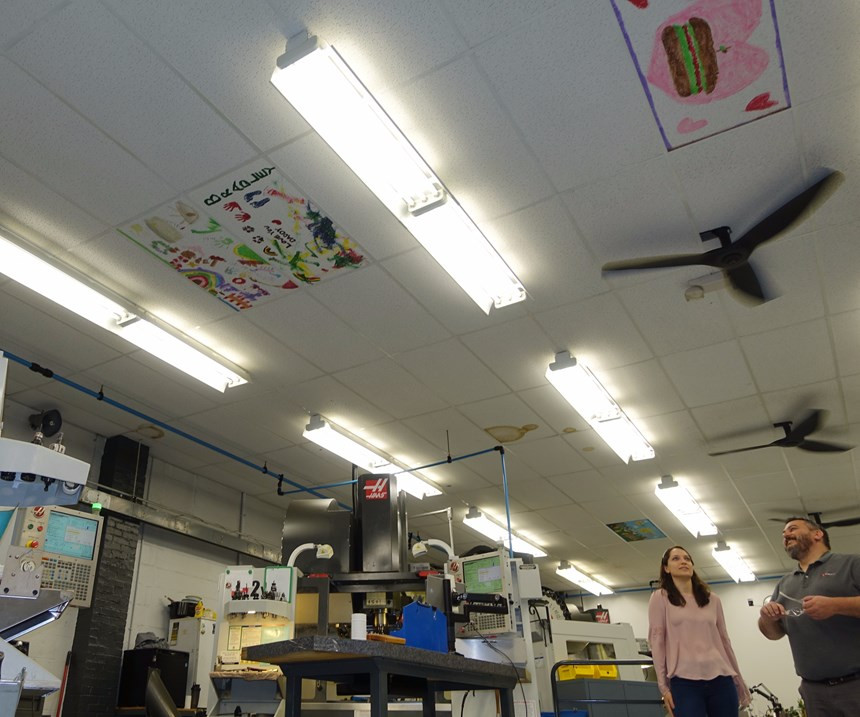 People look at decorated ceiling tiles at L&S Machine