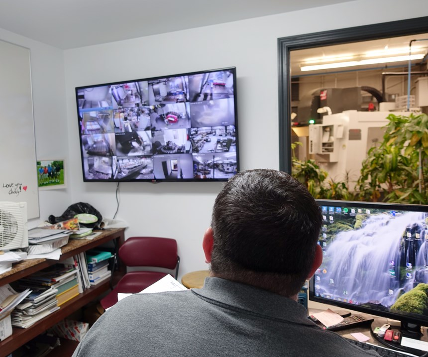Shop manager has monitors showing various parts of machine shop