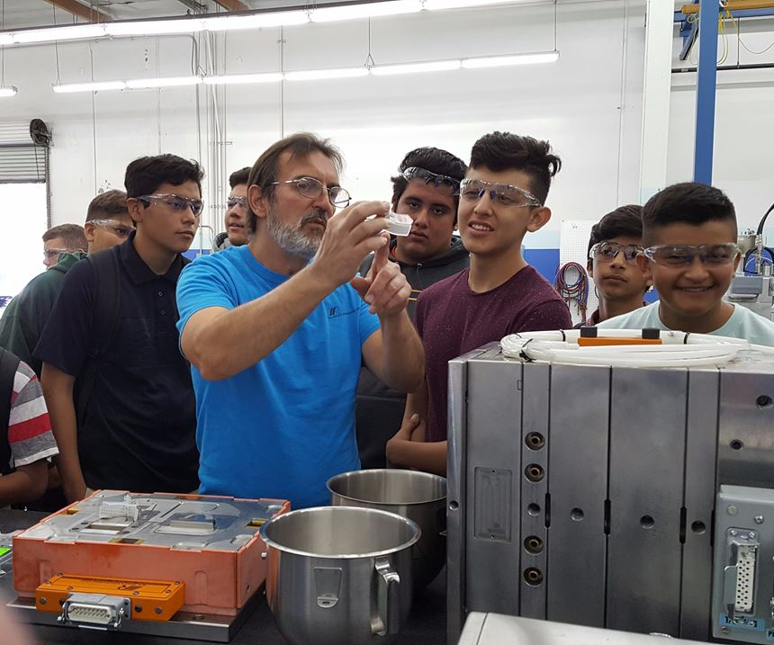 Graham Ballard, lead mold maker at M.R. Mold and Engineering, show visiting students a liquid silicone rubber (LSR) part