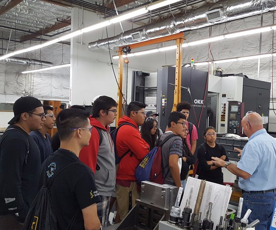 Ray Shapland, project engineering manager, talks about CNC programming with a group of students from Lou Vue's class at Valley High School, Santa Ana