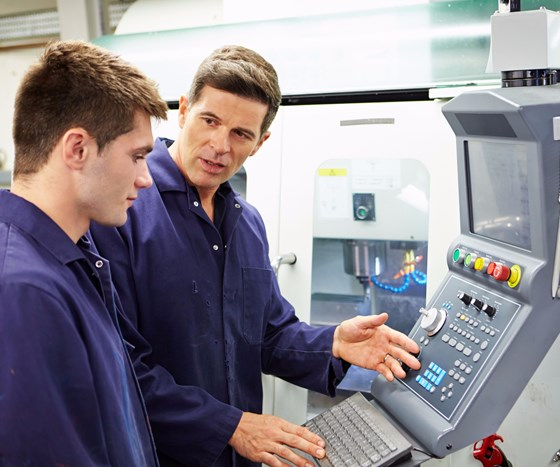 man teaching young machinist
