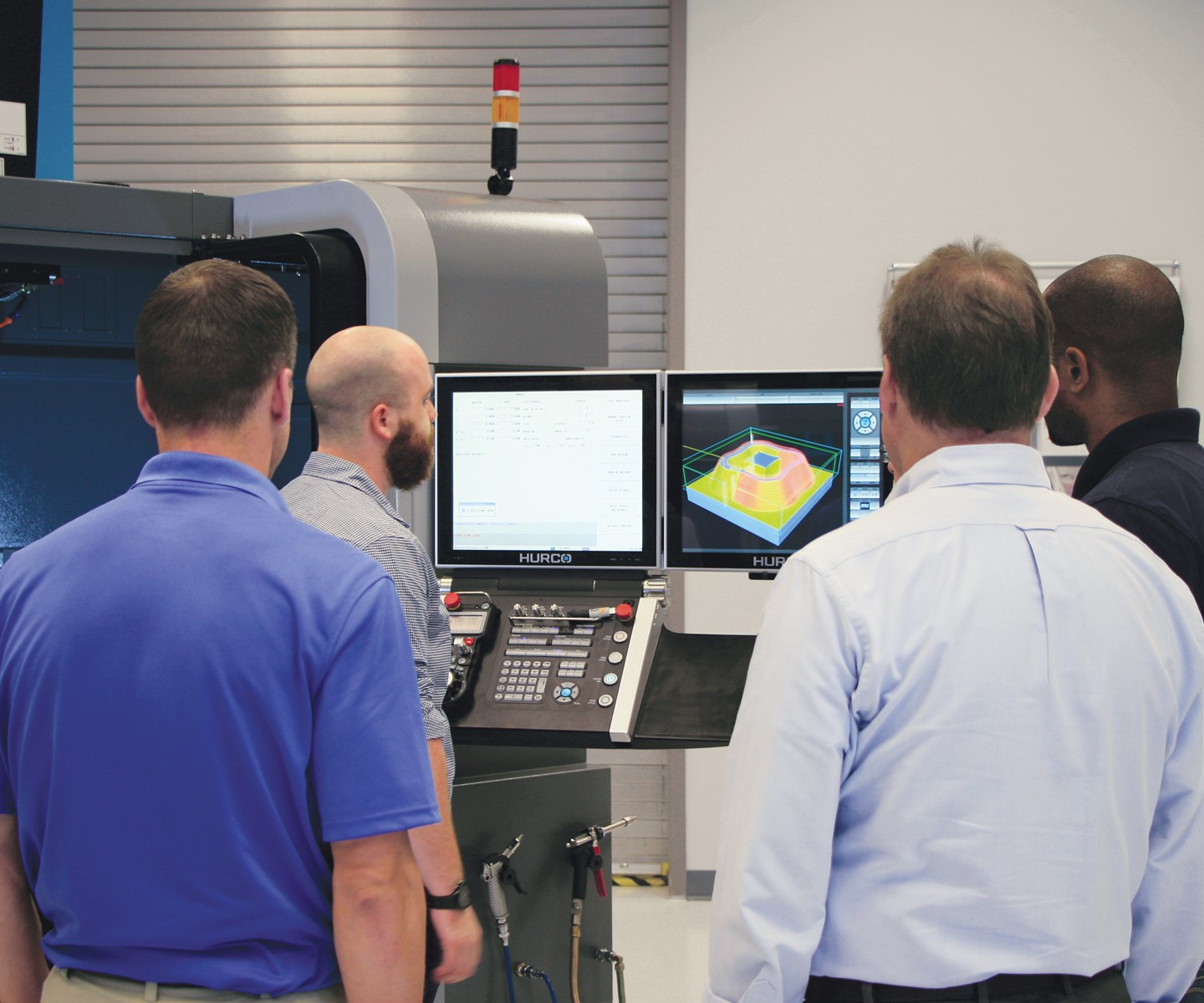 seminar attendees around a machine tool