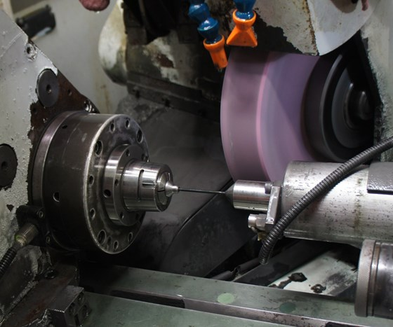 Grinding wheel and fixturing are visible in the workzone of a machine set up to grind between centers, a process that is generally more complicated than centerless grinding.