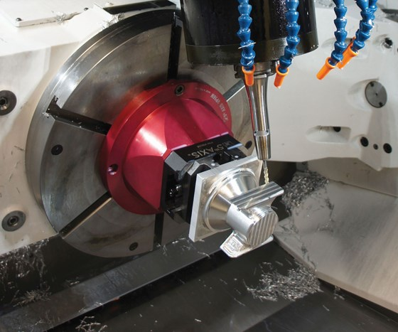 A five-axis machine cuts an aerospace part gripped in a dovetail workholding device.