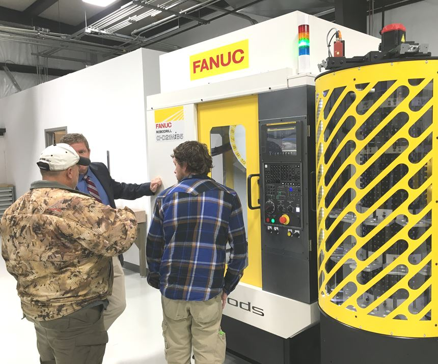 Attendees gather around a Fanuc Robodrill fitted with a robotic arm for transferring parts from the integrated storage unit to the worktable.