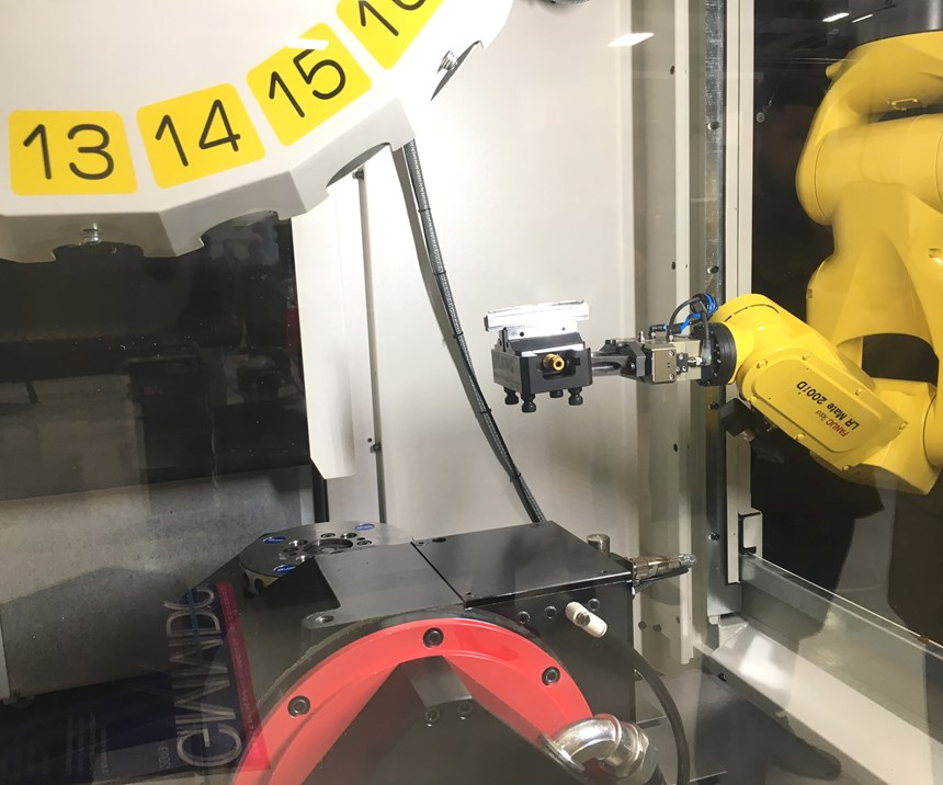 A robot arm transfers a palletized workpiece from a storage magazine to the workzone of a Fanuc Robodrill VMC.