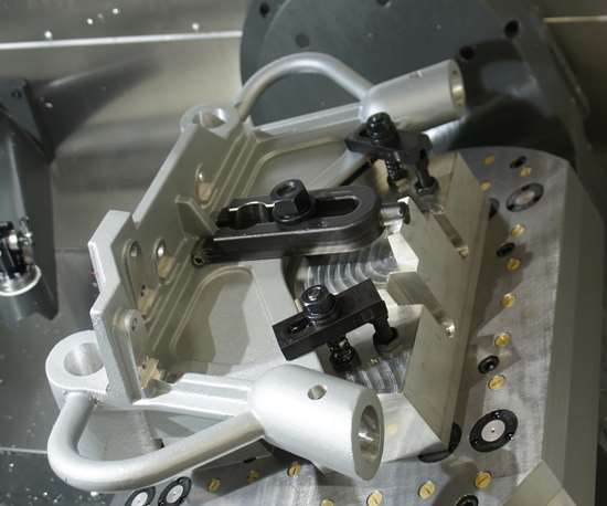A five-axis table tilts to provide spindle access to bores on a part held in a custom workholding fixture.