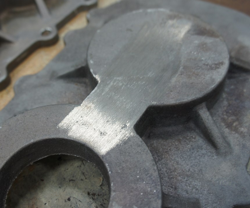 The marks on this component indicate where extra material was ground off at the foundry. The results of such work tend to vary from part to part.