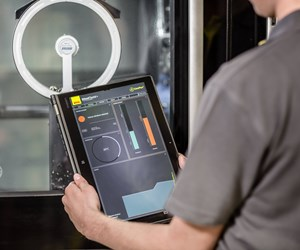 A machinist uses a tablet to monitor cutting conditions via embedded sensors in a CoroPlus Silent Tool from Sandvik Coromant.