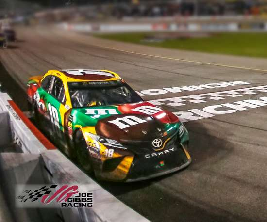 The No. 18 M&Ms Toyota Camry driven by Kyle Busch rounds a curve during a NASCAR race.