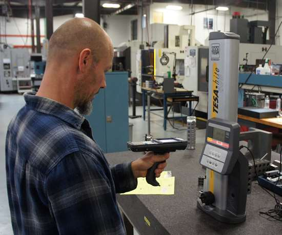 Machinist Dan Aldrich uses a handheld unit to scan the barcode on a height gage before use.