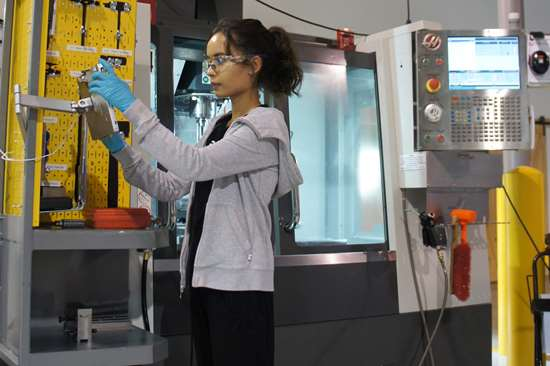 Plethora machinist Nemesis Contreras uses a tablet at her workstation in an example of machine shop digitalization