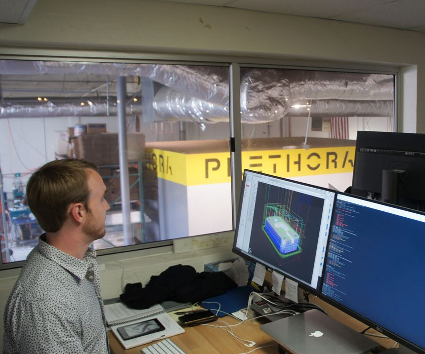 in a second-floor office with a window overlooking the shop, a computation geometry engineer works on his computer to improve and expand machine shop digitalization