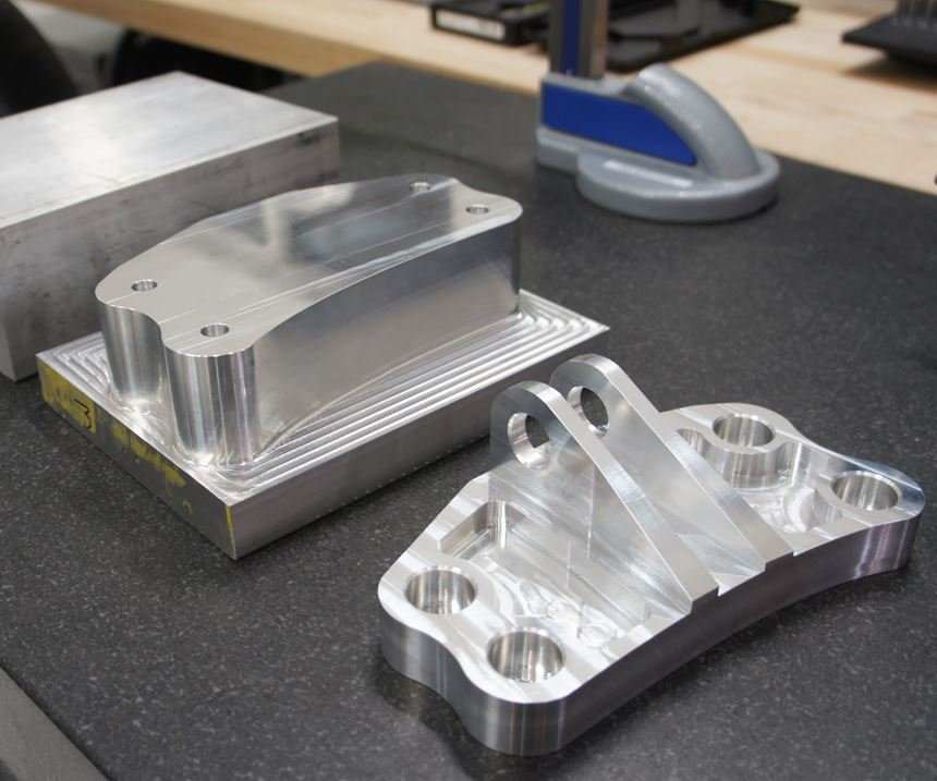 An example of a roughly rectangular custom machined part, featuring holes, pockets and other three-axis geometry, that was produced entirely via automated CAM.
