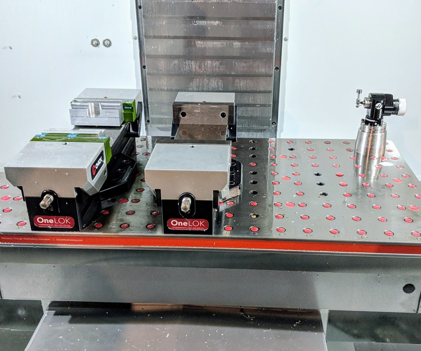 Two quick-change vises arrayed on a VMC table for custom machining
