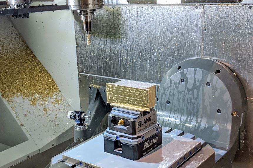 A rectangular part set up on a five-axis machining center for custom machining